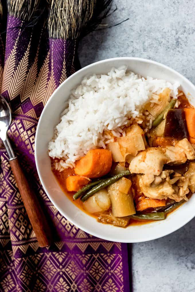 An image of a bowl of Cambodian Chicken Red Curry, known as Somlar Kari Saek Mouan or sometimes Khmer Red Curry, with rice.