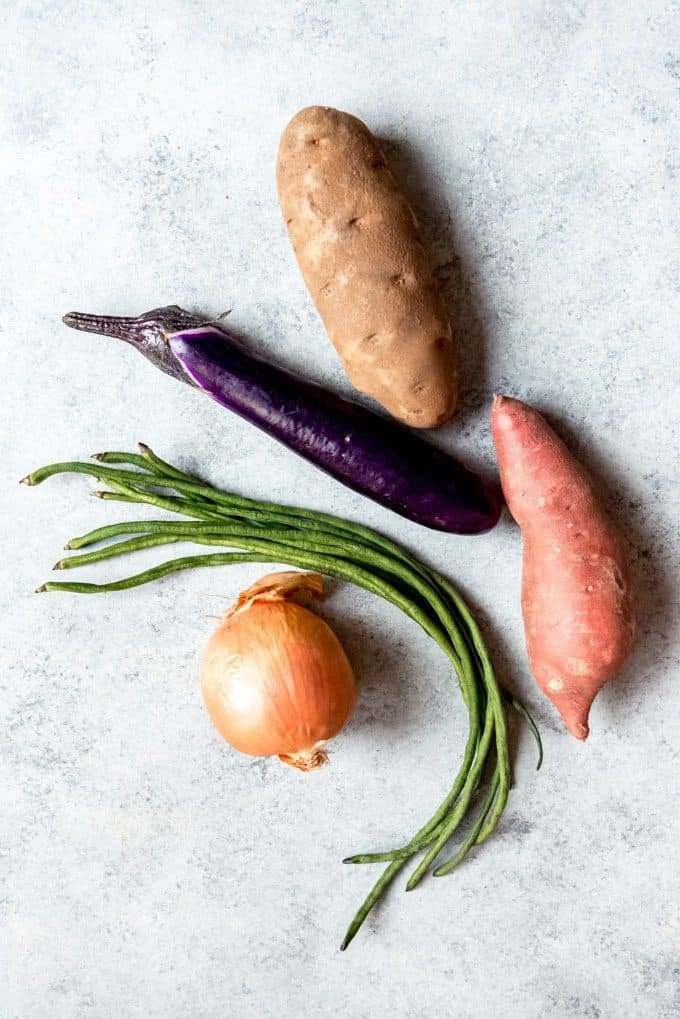 An image of a potato, sweet potato, eggplant, yardlong beans, and onion.