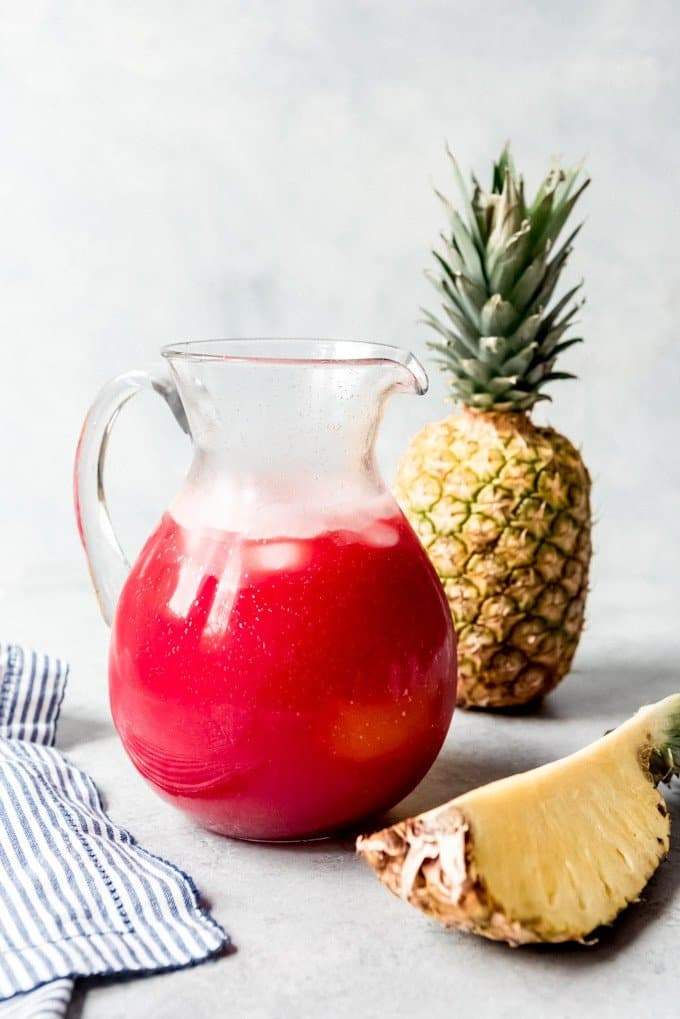 An image of a large pitcher of tropical fruit punch next to a sliced pineapple.