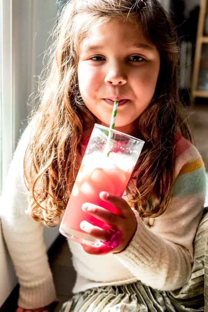 An image of a child sipping a glass of homemade Hawaiian punch.