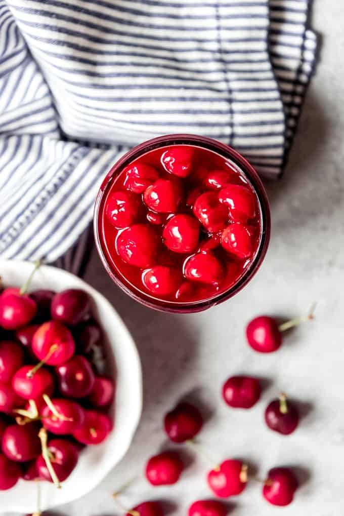 Fresh cherry pie filling next to a bowl of cherries.