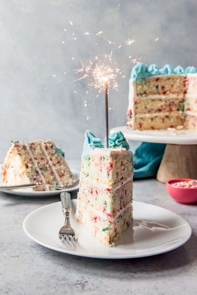 An image of a slice of birthday cake with a sparkler in it.