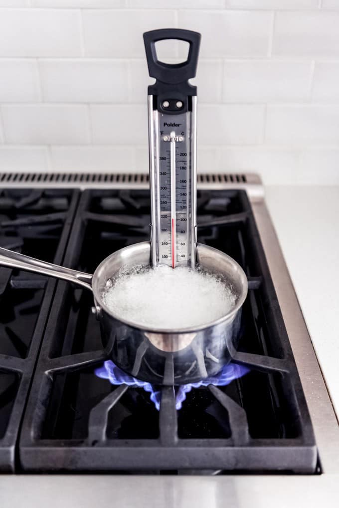 An image of a saucepan with sugar, corn syrup, and water on the stove with a candy thermometer in it.