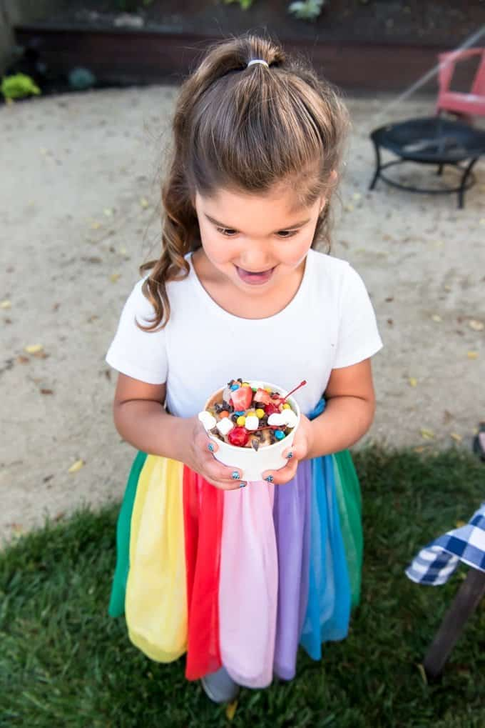 An image of a child holding an ice cream sundae.