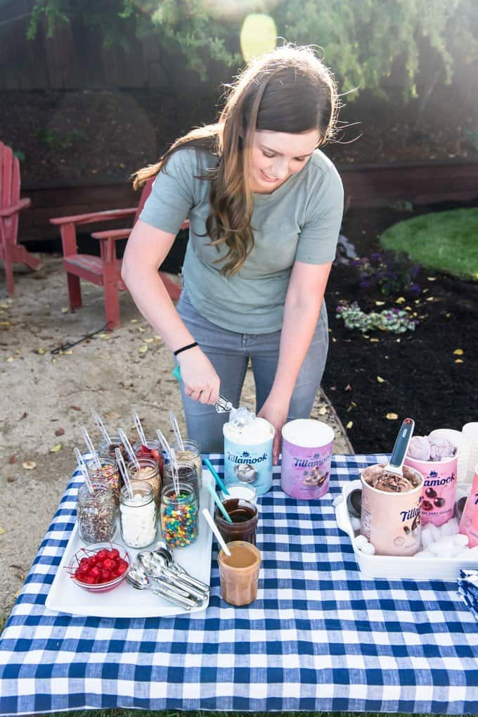 An image of a woman scooping ice cream with a bunch of toppings nearby for an ice cream sundae bar.