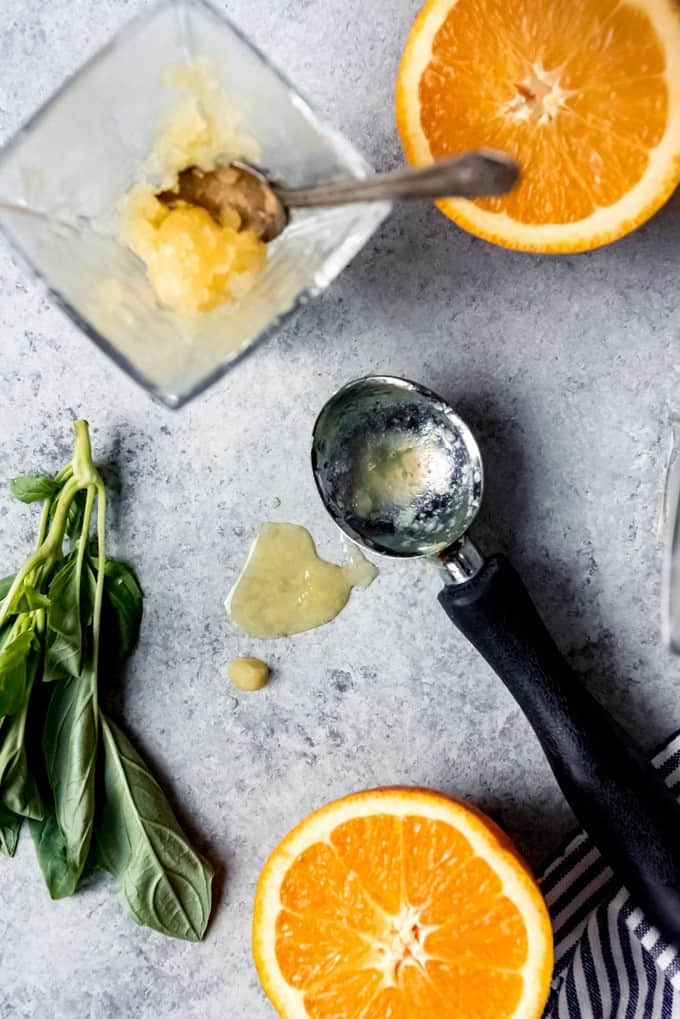 An image of an ice cream scoop, sliced oranges, and melted orange basil granita.