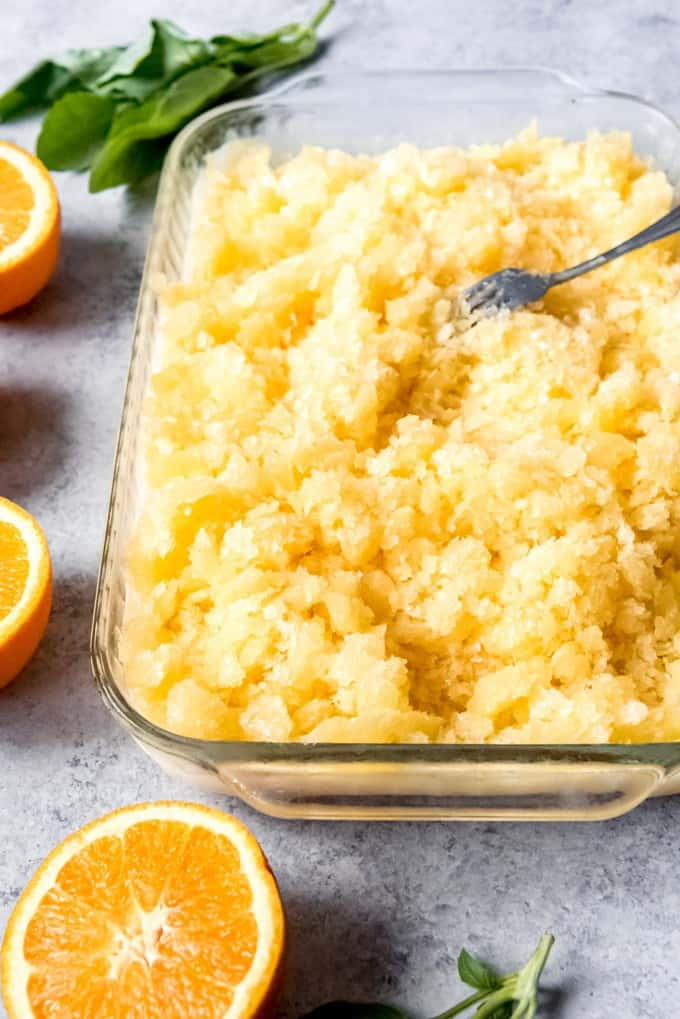 An image of a large dish filled with orange basil coconut granita.
