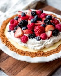 An image of a white chocolate cream pie topped with whipped cream and fresh mixed berries.
