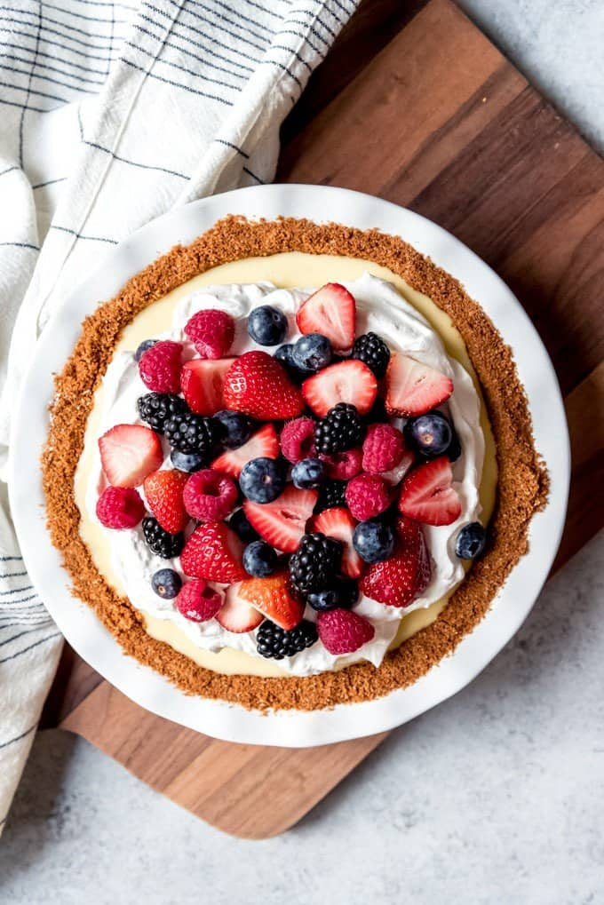 An image of a white chocolate cream pie topped with sweetened whipped cream and lots of fresh berries.