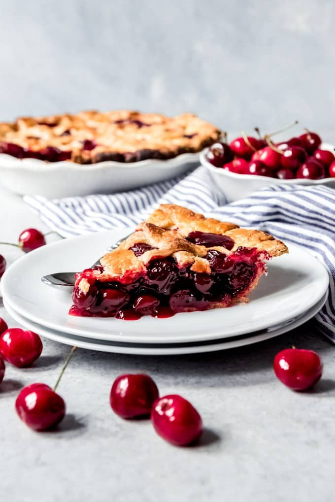An image of a slice of homemade cherry pie on a plate.