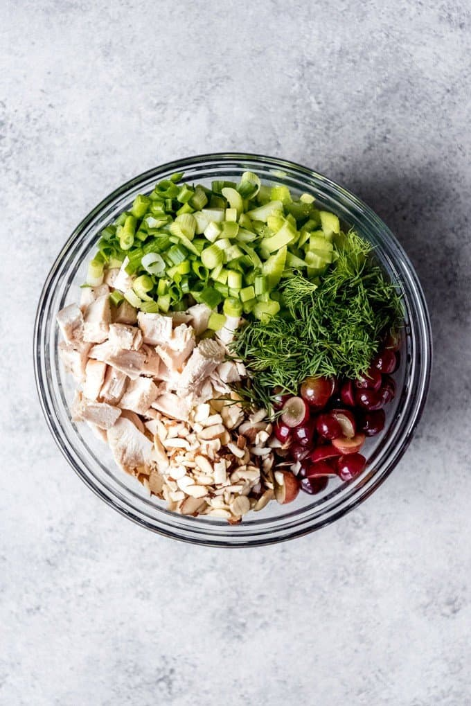 An image of a bowl with the ingredients for a classic chicken salad recipe.