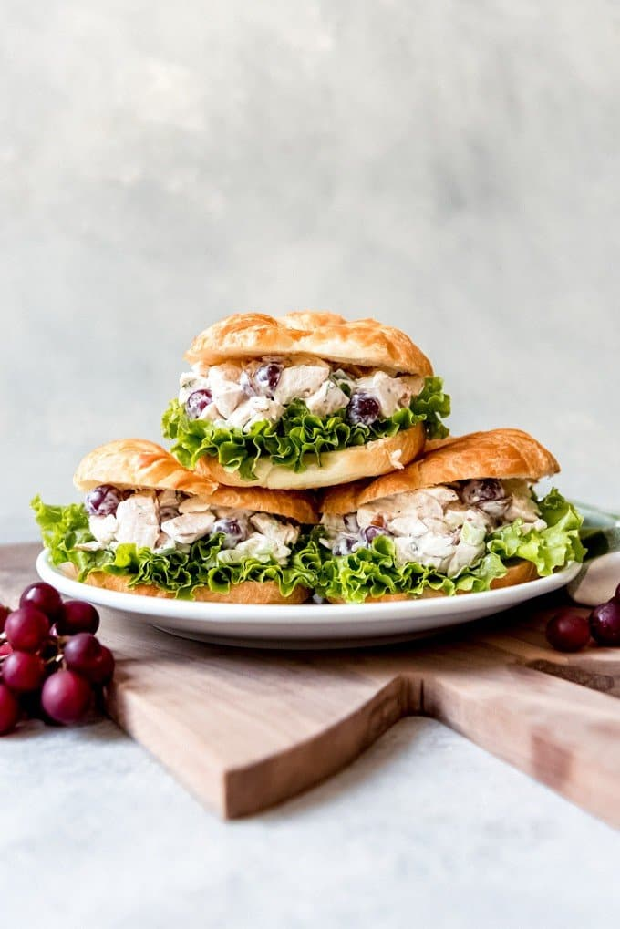 An image of three chicken salad sandwiches on croissants, stacked on a plate.