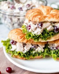 An image of chicken salad sandwiches with grapes stacked on a plate.