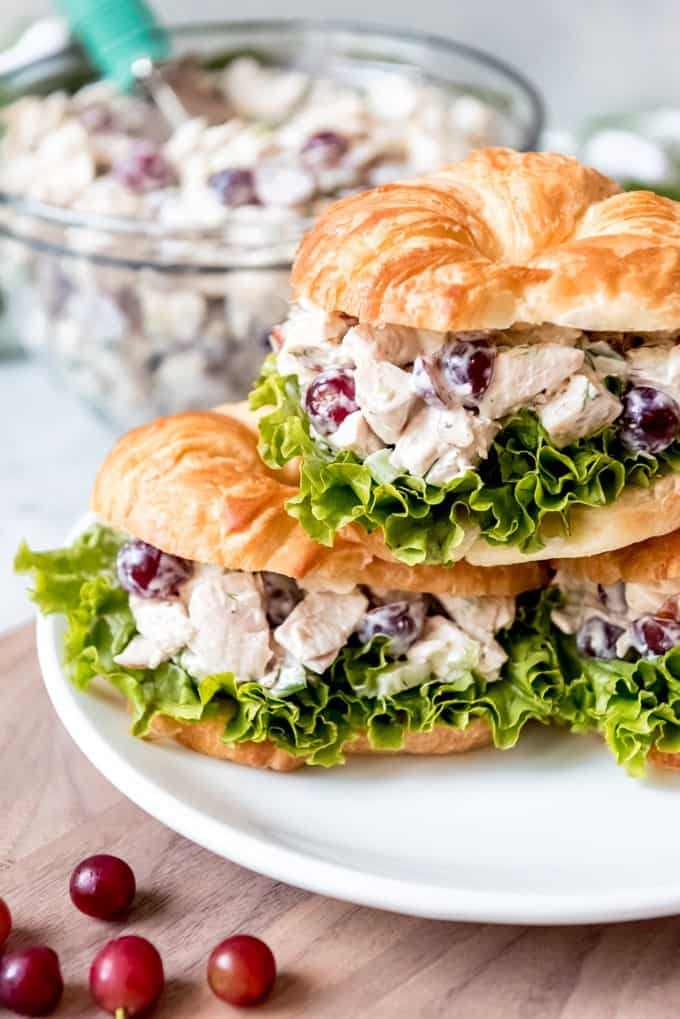 three stacked chicken salad sandwiches on a white plate