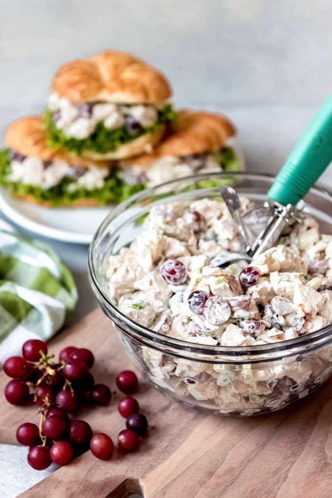 An image of a bowl of homemade chicken salad sitting next to a plate of chicken salad sandwiches on croissants.