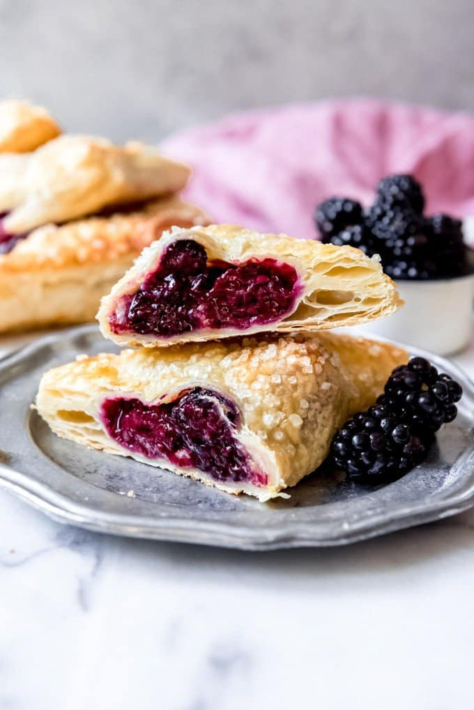 An image of a blackberry hand pie or turnover cut in half on a plate.