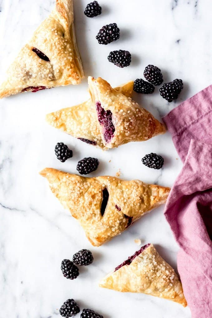 An image of triangle-shaped blackberry turnovers on a marble slab with fresh blackberries scattered around.
