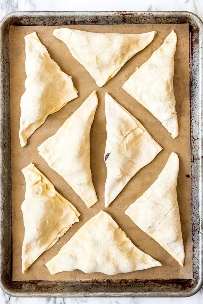 An image of unbaked blackberry turnovers on a parchment-lined baking sheet.
