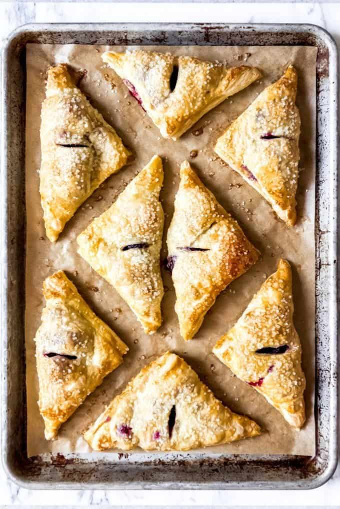 An image of baked blackberry turnovers on a parchment-lined baking sheet.