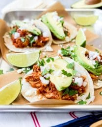 An image of smoky shredded chicken tinga tacos topped with sliced avocado, cilantro, chopped onion, cotija cheese, and lime juice.