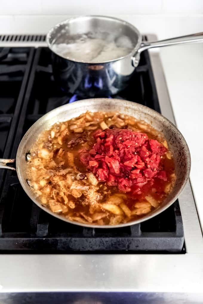 An image of a pan with sauteed onion, fire-roasted tomatoes, chipotle peppers, and other spices for making chicken tinga tacos.