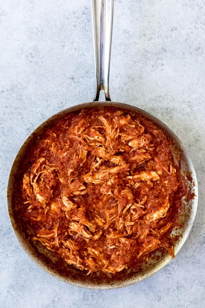 An image of shredded chicken tinga taco filling in a pan.