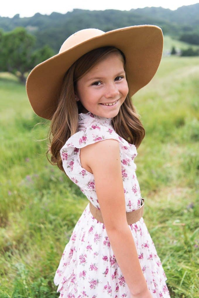 An image of a girl in a hat and floral dress.
