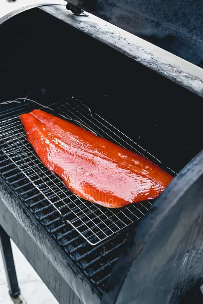An image of a large piece of salmon on a pellet smoker.