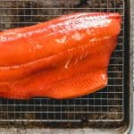 An image of a piece of hot smoked salmon on a wire rack.