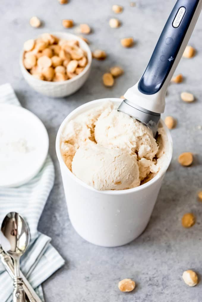An image of a container of coconut macadamia nut ice cream with an ice cream scoop in it.