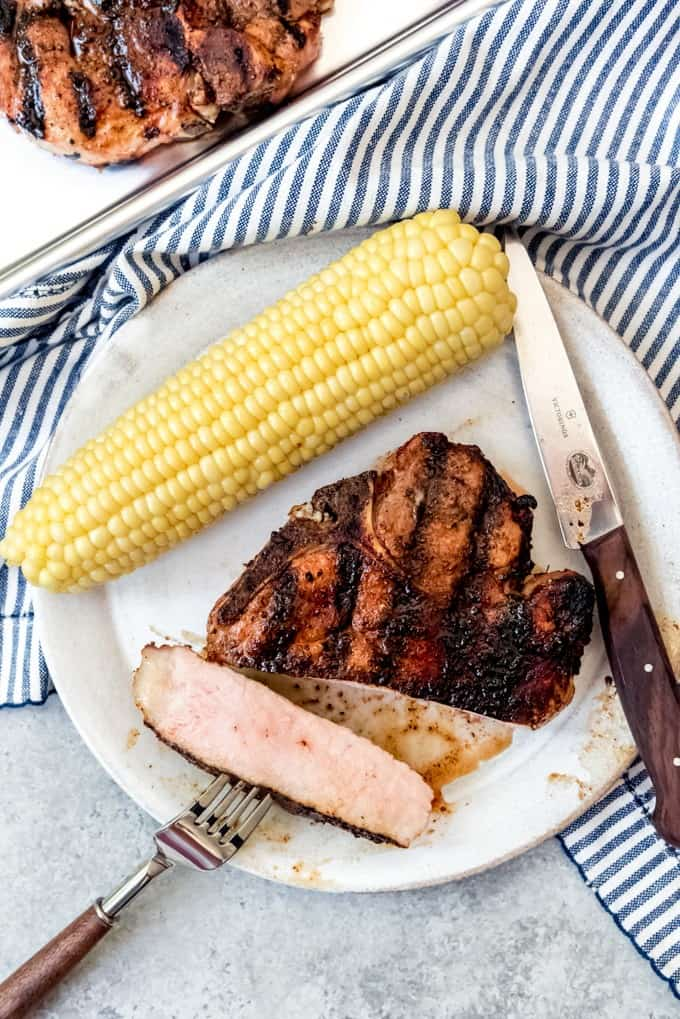 An image of a slice of grilled pork chop with a blush of pink on the inside on a plate with boiled corn on the cob.