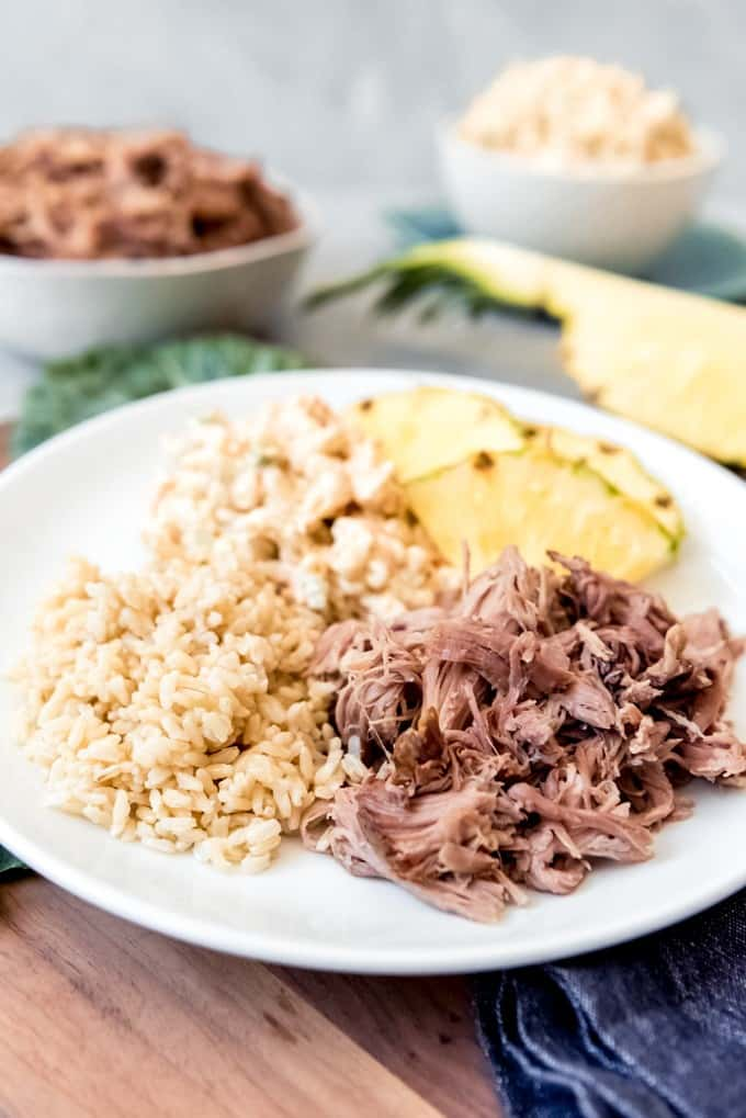 An image of shredded Kalua pork on a plate with rice, macaroni salad, and fresh pineapple.