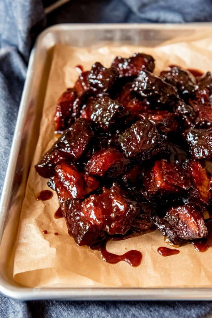 An image of smoked pork belly burnt ends on a baking sheet.