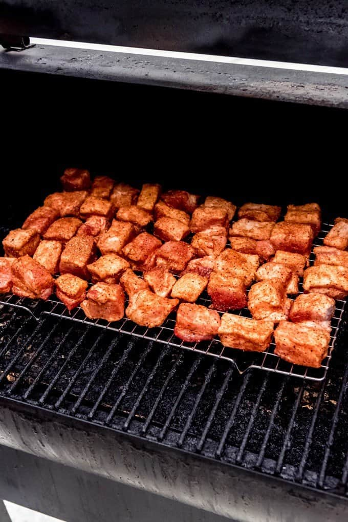 An image of pork belly on a Traeger smoker grill.