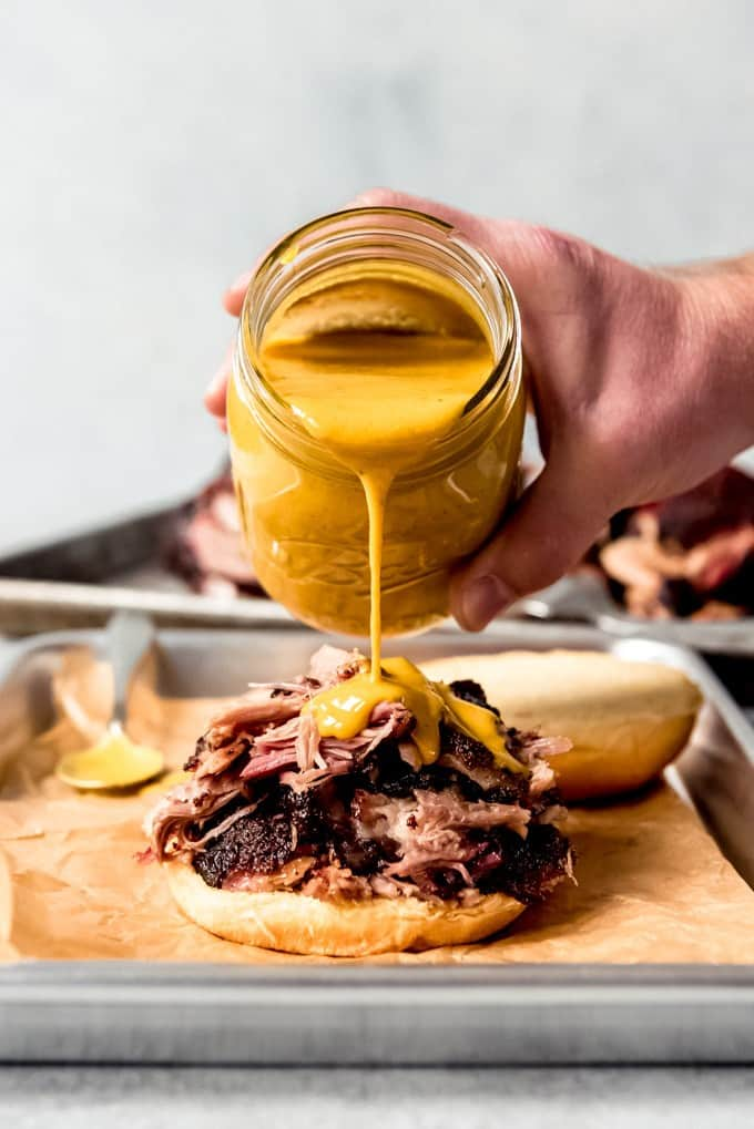 An image of Carolina gold BBQ sauce being poured over pulled pork on a bun.
