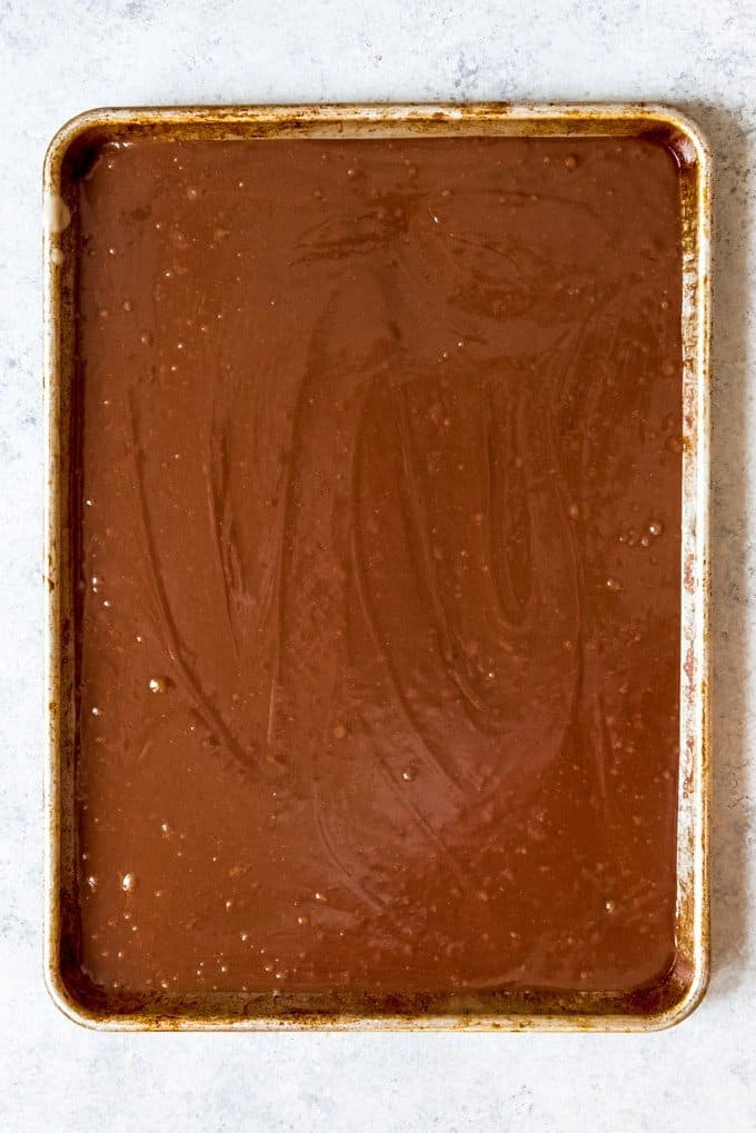 An image of chocolate cake batter poured into a baker's half-sheet pan.