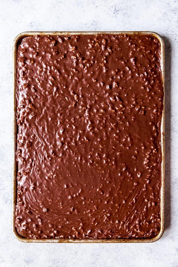 An image of a Texas sheet cake with warm chocolate pecan icing poured over the top.