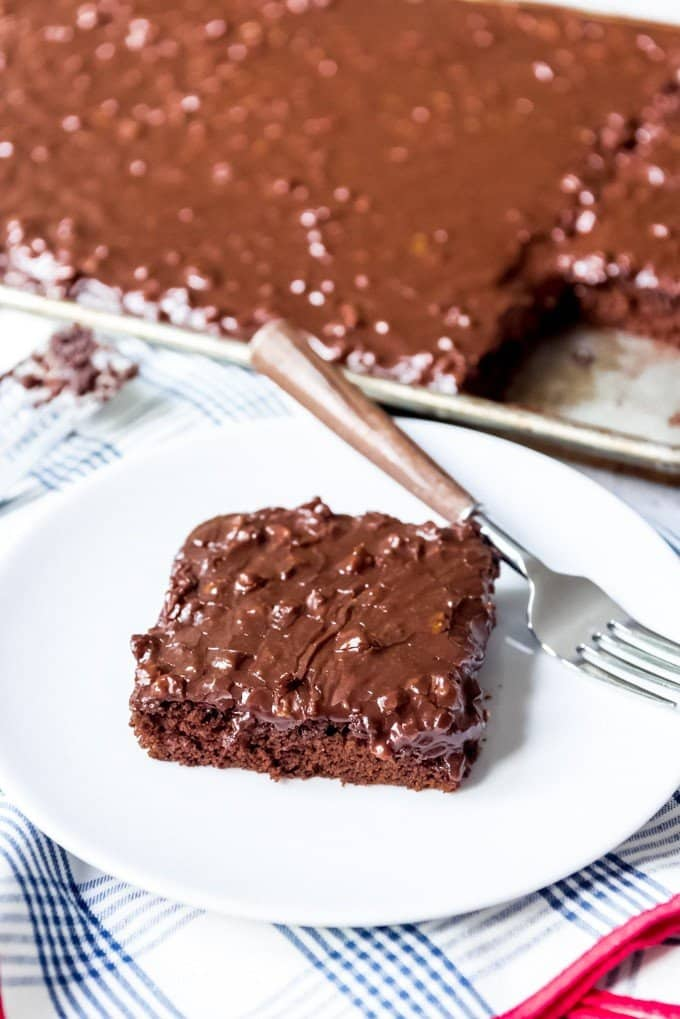An image of a slice of chocolate sheet cake on a white plate.