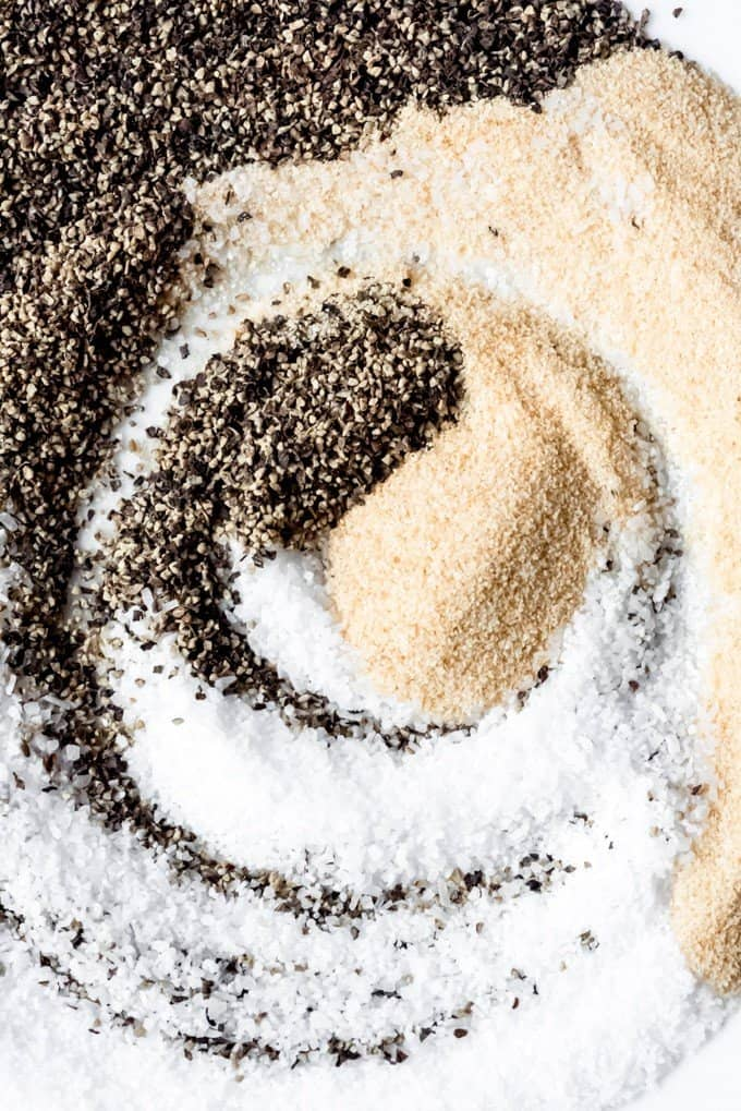 An image of salt, pepper, and garlic powder swirled on a plate.