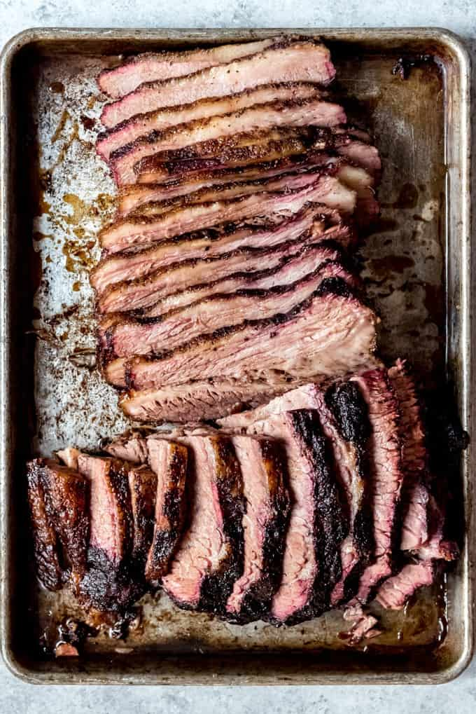 An image of sliced smoked brisket on a baking sheet.