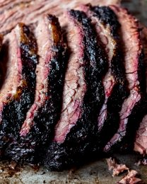 An image of slices of Texas-style smoked beef brisket with a dark bark and pink smoke ring.