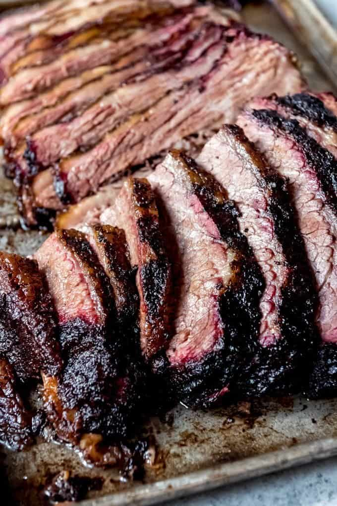 An image of tender, juicy slices of smoked brisket with a smoke ring and dark crusty bark around the edges.