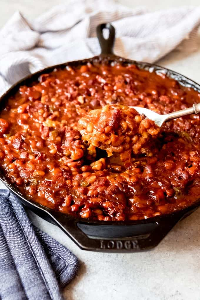 An image of a large serving spoon lifting up a scoop of baked beans.