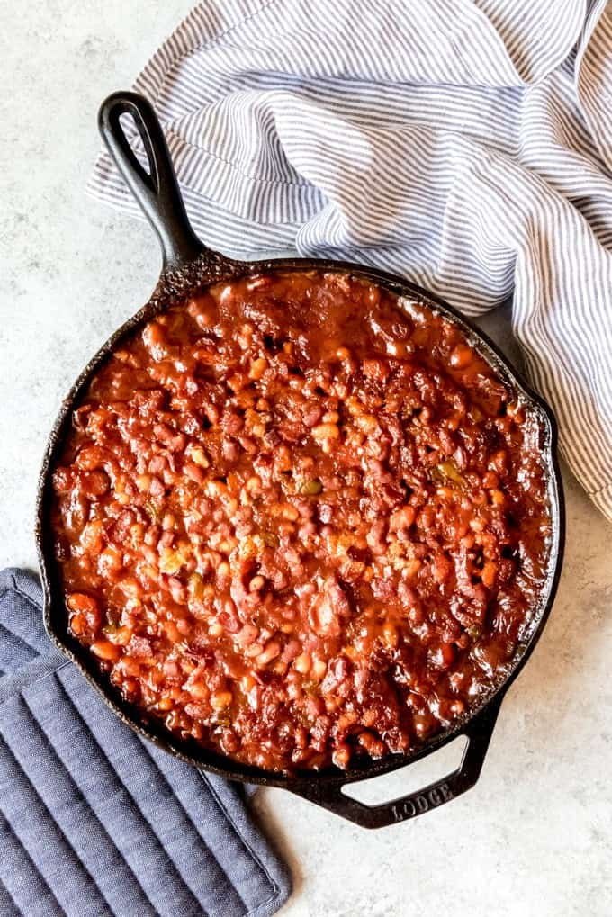 An image of a large cast iron skillet filled with potluck baked beans.