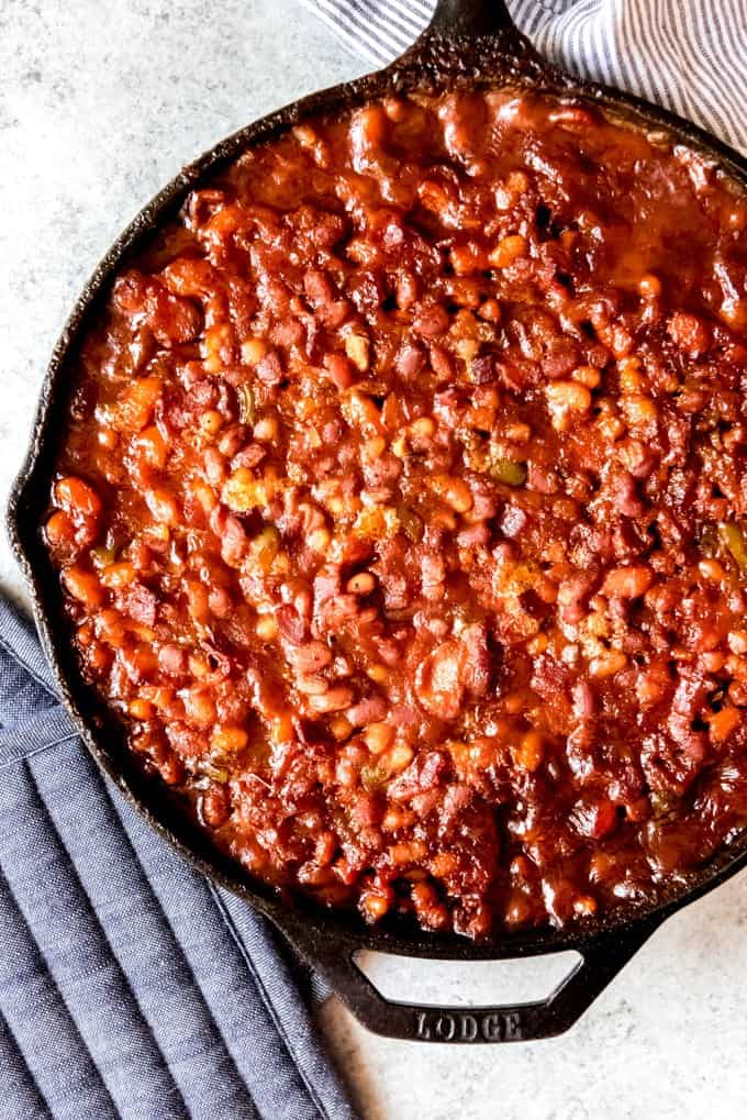 An image of a large cast iron pan filled with homemade baked beans.