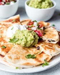 An image of chicken quesadillas piled on a plate with guacamole, sour cream, and pico de gallo.
