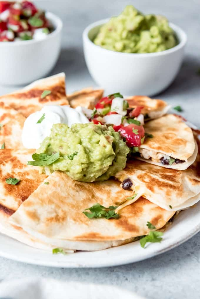 An image of chicken quesadillas with black beans, green onions, and lots of guacamole, sour cream, and pico de gallo piled on top.