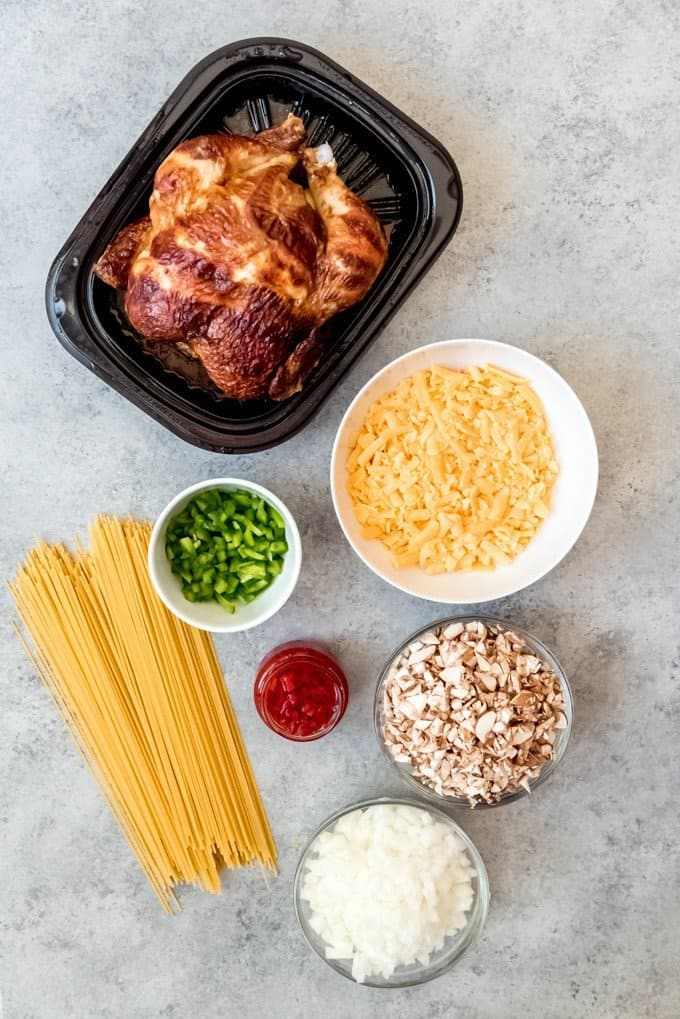 An image of a rotisserie chicken, uncooked spaghetti noodles, chopped onion, chopped green bell pepper, diced onions, shredded cheddar cheese, and a jar of pimentos.