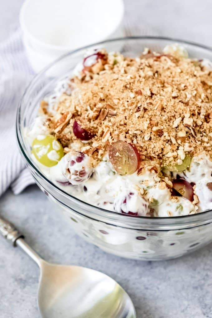 An image of a large bowl of creamy grape salad with brown sugar and pecan topping.