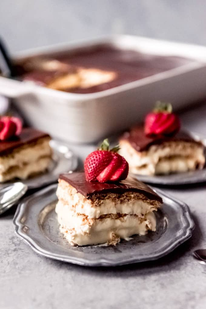An image of a layered icebox cake dessert with softened graham crackers, creamy pudding and whipped cream, and chocolate glaze on top.